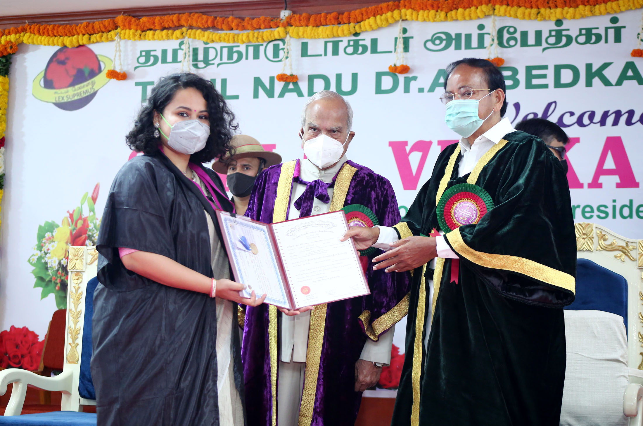 The Vice President, Shri M. Venkaiah Naidu presenting degrees to the students at the 11th Convocation of the Tamil Nadu Dr. Ambedkar Law University, in Chennai, Tamil Nadu on February 27, 2021. The Governor of Tamil Nadu, Shri Banwarilal Purohit is also seen.